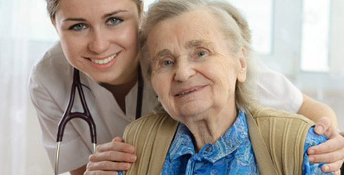 A lady with her hands on the shoulders of the older lady in front of her